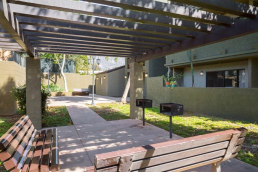 BBQ area on cement patio with wooden cabana above, two grills and 2 benches